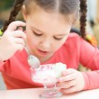 Little girl is eating ice-cream in parlor - Stock Photo