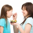 Mother is feeding her daughter with fruit salad — Stock Photo