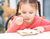 Little girl is eating cake in parlor — Stock Photo