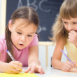 Little girls are writing using a pen — Stock Photo #23550733