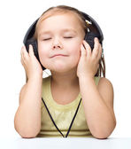 Little girl is enjoying music using headphones — 图库照片