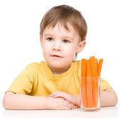 Niño está comiendo zanahoria — Foto de Stock