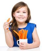 Linda niña está comiendo zanahoria — Foto de Stock