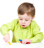 Little boy is drawing on white paper using crayon — Stock Photo