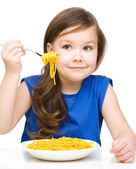 Klein meisje is eten spaghetti — Stockfoto