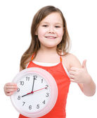 Little girl is holding big clock — Stock Photo