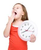 Little girl is holding big clock — Foto de Stock