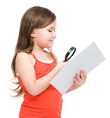 Girl is looking at big paper using magnifier — Стоковое фото