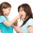 Daughter is feeding her mother with fruit salad — Stock Photo