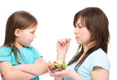 Mother is trying to feed her daughter — Stock Photo