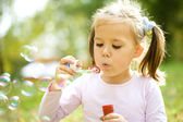 Little girl is blowing a soap bubbles — Stockfoto