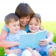 Family is reading book — Stockfoto