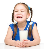 Sad little girl with a glass of milk — Stock Photo