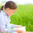 Little girl is reading a book outdoors — Stock Photo #26003239