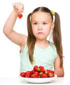 Little girl is eating strawberries — Stock Photo