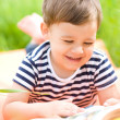 Stock Photo: Little boy is reading book