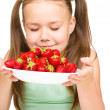 Stock Photo: Cheerful little girl is smelling strawberries