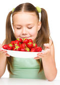 Cheerful little girl is smelling strawberries — Stock Photo