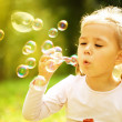 Little girl is blowing a soap bubbles — Stock Photo #27752937