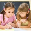 Little girls are writing using a pen — Stock Photo #27752959