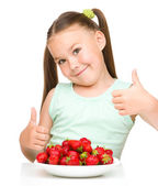 Happy little girl is eating strawberries — Stock Photo