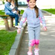 Stock Photo: Happy little girl is skating on rollers