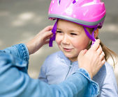 Mother is helping her daughter with safety helmet — Stock Photo