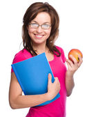 Young student girl is holding book and apple — Стоковое фото