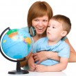 Mother is looking at globe with her son — Stock Photo