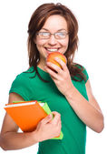 Young student girl is holding book and apple — Stock Photo