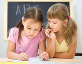 Little girls are writing using a pen — Stock Photo