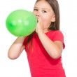 Little girl is inflating green balloon — Stock Photo