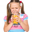 Little girl unwillingly drinking orange juice — Stock Photo