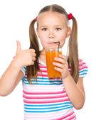 Little girl is drinking carrot juice — Stock Photo