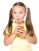 Little girl is drinking carrot juice — Stock Photo