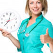 Young lady doctor is holding clock showing seven — Photo