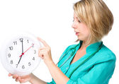 Young lady doctor is holding clock showing seven — Stock Photo