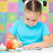 Stock Photo: Little girl is writing using pen