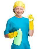 Mladá žena s čisticí kapalina a houba — Stock fotografie