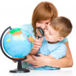 Mother is looking at globe with her son — Stock Photo #30110163