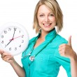 Young lady doctor is holding clock showing seven — Stockfoto