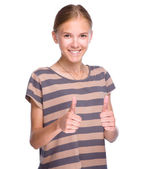 Young girl is showing thumb up gesture — Stock Photo