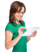 Young cheerful woman is using tablet — Stock Photo