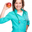 Young lady doctor is holding a red apple — Foto de Stock