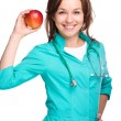 Young lady doctor is holding a red apple — Stok fotoğraf