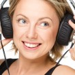 Young woman enjoying music using headphones — Stock Photo #32207507