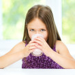 Stock Photo: Little girl with a glass of milk