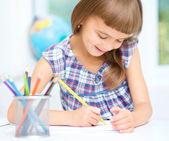 Little girl is drawing using pencils — Stok fotoğraf