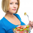 Young attractive woman is eating salad using fork — Stock Photo