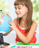 Little girl is examining globe — Stock Photo